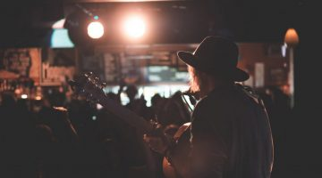 musician playing guitar and singing at concert